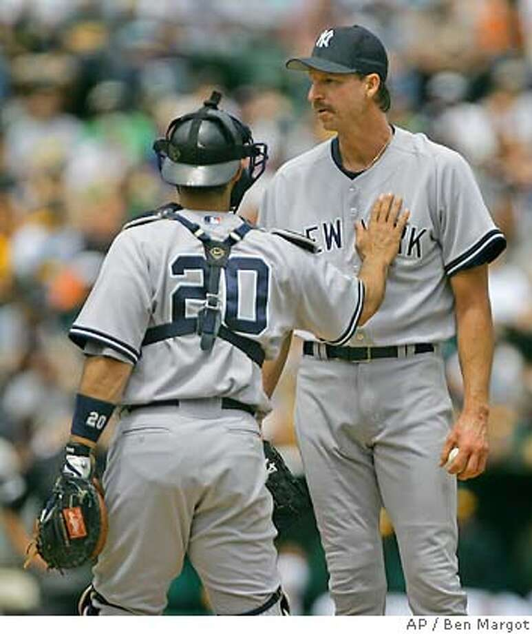 New York Yankees catcher Jorge Posada (20) calms down pitcher Randy Johnson in the first inning against the Oakland Athletics Sunday, May 15, 2005, in Oakland, Calif. (AP Photo/Ben Margot) Photo: BEN MARGOT