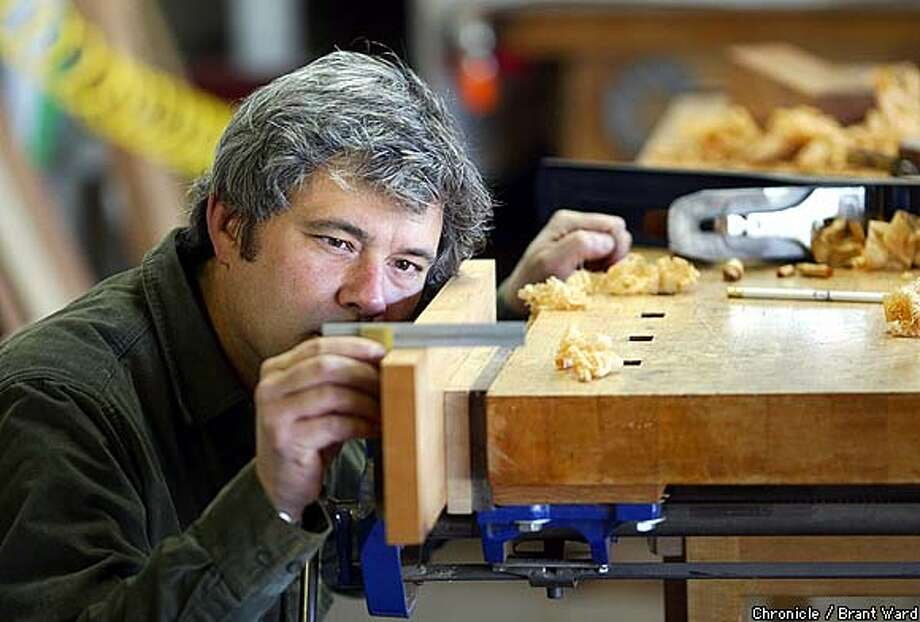 Master wood craftsman Michael Cullen checks out the flatness of a piece of wood in his Petaluma studio...he is currently teaching David Hirsch the intricasies of woodworking. By Brant Ward/Chronicle Photo: BRANT WARD