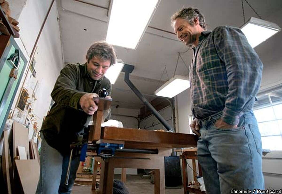 Michael Cullen, left, and David Hirsch smile as they work on a piece of mahogany during an apprentice lesson. Cullen is teaching Hirsch the fine points of woodworking in his Petaluma studio. By Brant Ward/Chronicle
