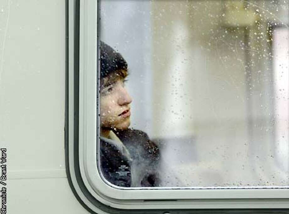 A young man was lost in thought as he sat at the back of a Muni streetcar on Market Street and watched the rain come down Wednesday. By Brant Ward/Chronicle Photo: BRANT WARD