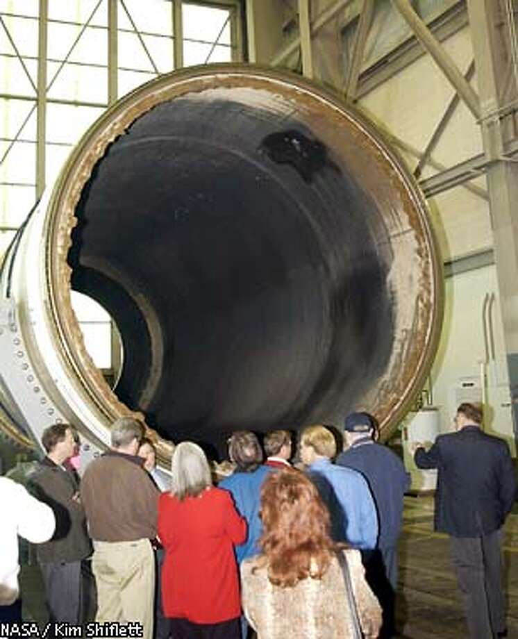 Members of the Columbia accident investigating team look over a segment of a solid rocket booster in a hangar at the Cape Canaveral Air Force Station in Cape Canaveral, Fla. Thursday Feb. 13, 2003. The team, which is looking a components not from Columbia's breakup, is in the area as part of the investigation into the shuttle accident that killed seven astronauts.(AP Photo/NASA / Kim Shiflett) Photo: KIM SHIFLETT
