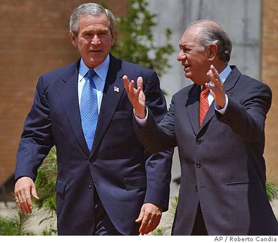 Chilean President Ricardo Lagos, right, gestures while escorting President Bush upon arrival at Santiago, Chile for the first meeting of this year's Asia-Pacific Economic Cooperation (APEC) Summit of 21-member-economies. (AP Photo/Roberto Candia) Photo: ROBERTO CANDIA
