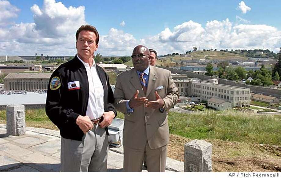 Gov. Arnold Schwarzenegger, left, and Rodrick Hickman, secretary of the the Youth and Adult Correctional Agency, stand on a hillside above Folsom State Prison, in Folsom, Calif., Tuesday, May 10, 2005. Schwarzenegger was at the prison to sign legislation that, as of July 1, 2005, would place the Youth and Adult Correctional Agency into the Department of Corrections and Rehabilitation.(AP Photo/Rich Pedroncelli) Ran on: 05-11-2005  Gov. Arnold Schwarzenegger (left) and Roderick Hickman, secretary of the Youth and Adult Correc- tional Agency, stand on a hillside above Folsom State Prison, where the governor signed a bill re- organizing the corrections system. Photo: RICH PEDRONCELLI