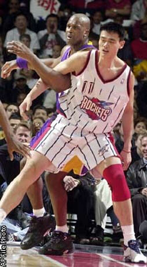 ** ADVANCE FOR SUNDAY, FEB. 9 **FILE**Houston Rockets center Yao Ming (11) and Los Angeles Lakers center Shaquille O'Neal tangle in the first half of a game Jan. 17, 2003, in Houston. During the game, the first contest between the two NBA stars, Yao blocked several of O'Neal's shots but the Laker center outscored Yao 31 to 10. (AP Photo/Pat Sullivan) Photo: PAT SULLIVAN