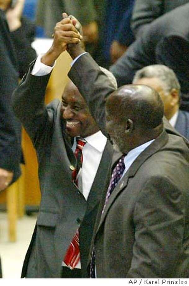 Sudanese Vice President Ali Osman Taha, left, holds hands with Sudan People's Liberation Movement leader John Garang, right, Friday, Nov. 19, 2004 during the U.N Security Council meeting in Nairobi, Kenya. Sudanese government and rebel officials signed an agreement Friday promising to end the 21-year civil war in Sudan by the end of the year in front of the U.N. Security Council holding a special meeting in Africa.The security council passed a new resolution on Sudan on Friday, offering to support peace processes in the country aimed at ending two civil wars that have left millions dead and many more homeless. (AP Photo/Karel Prinsloo) Ran on: 11-20-2004  Raising their arms in victory, Sudanese Vice President Ali Osman Mohammed Taha (left) and rebel leader John Garang could serve together. Photo: KAREL PRINSLOO