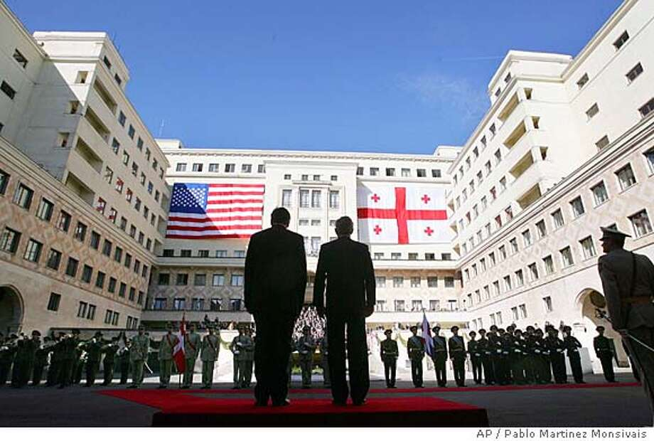 U.S. President George W. Bush, right, and Georgian President Mikhail Saakashvili, left, stand for the playing of the National Anthems of the U.S. and Georgia, during arrival ceremonies in the courtyard of the Georgian Parliament Building Tuesday, May 10, 2005 in Tbilisi, Georgia. Bush arrived in the ex-Soviet republic of Georgia on a visit that Georgians hope will notch up the pressure on Russia to respect this young democracy on its doorstep. (AP Photo/Pablo Martinez Monsivais) Photo: PABLO MARTINEZ MONSIVAIS