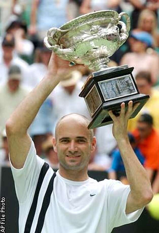**FILE**Andre Agassi displays the winner's trophy after defeating Rainer Schuettle in the men's final at the Australian Open Tennis Championships in Melbourne, Sunday Jan. 26, 2003. Agassi and Martina Navratilova won Grand Slam titles again and Jerry Rice scored one more Super Bowl touchdown. Elite athletes are playing at a higher level longer than ever, defying age and redefining limits and perceptions.(AP Photo/Steve Holland) Photo: STEVE HOLLAND