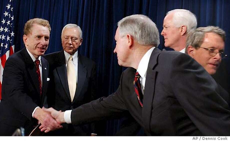 Senator Arlen Specter, R-Pa., shakes hands with Sen. Jeff Session, R-Ala., on Capitol Hill Thursday, Nov. 19, 2004, after Republicans members of the Senate Judciary Committee said they would support Specter as the next committee chairman, succeeding Sen. Orrin, R-Utah, second from left. In the background, are Sen. John Cornyn, R-Tex., second from right, and Sen. Mike DeWine. (AP Photo/Dennis Cook) Photo: DENNIS COOK