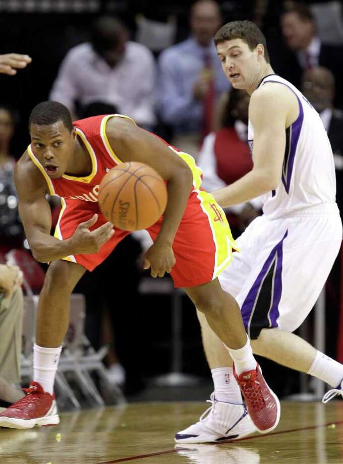 Houston Rockets' Kyle Lowry, left, keeps the ball from going out of bounds as Sacramento Kings' Jimmer Fredette, right, defends during the first quarter of an NBA basketball game Friday, Jan. 13, 2012, in Houston. Photo: David J. Phillip, AP / AP
