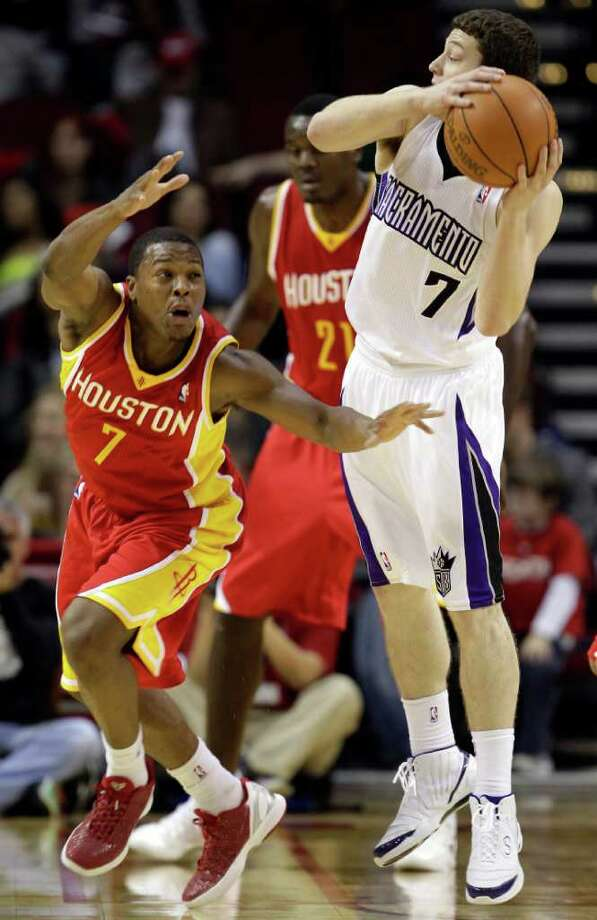 Houston Rockets' Kyle Lowry, left, tries to steal the ball from Sacramento Kings' Jimmer Fredette, right, during the third quarter of an NBA basketball game Friday, Jan. 13, 2012, in Houston. The Rockets defeated the Kings 103-89. Photo: David J. Phillip, AP / AP
