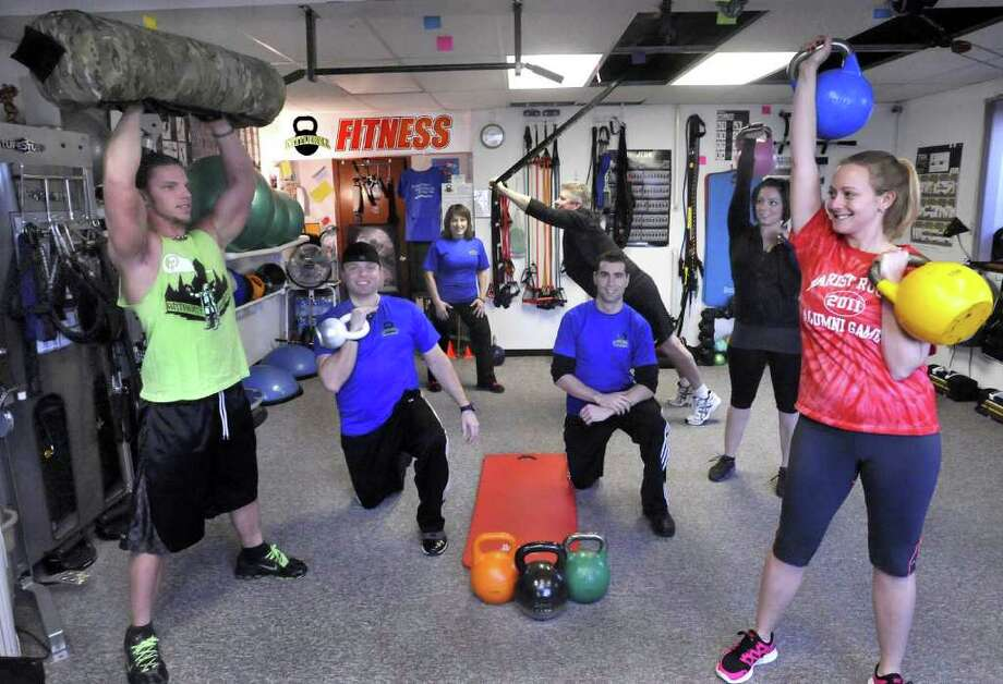 Trainers and clients are shown here at Kettlebell Fitness LLC, in Bethel Thursday, Jan. 19, 2012. From left are Brian Anthony, owner Andreas Washeim, Debra Rydziel, Manny Cabral, David Chiara, Erin Lionetti, and Danielle Hundt. Photo: Michael Duffy / The News-Times