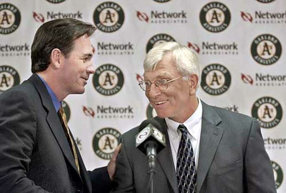** FILE **Oakland Athletics general manager Billy Beane, left, congratulates new A's manager Ken Macha during a news conference in Oakland, Calif., Oct. 29, 2002. A Boston Red Sox spokesman confirmed Saturday night, Nov. 9, that the A's have given them permission to talk to Beane about the same job with the Red Sox. (AP Photo/Paul Sakuma, File) Photo: PAUL SAKUMA
