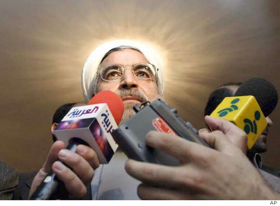 Iran's top nuclear negotiator, Hasan Rowhani, who is secretary of the Supreme National Security Council, speaks with media as a light shines from behind his head, after his meeting with French ambassador to Tehran, Francois Nicoullaud, British ambassador, Richard Dalton, and German ambassador, Paul von Maltzahn, at the Saadabad palace in Tehran, Iran, Sunday, Nov. 14, 2004. Iran has given the United Nations a written promise to fully suspend uranium enrichment, diplomats said on Sunday, in an apparent bid to dispel suspicions that Tehran wants to build a nuclear bomb. (AP Photo) Ran on: 11-15-2004  Iranian head negotiator Hassan Rowhani speaks to reporters as a light shines behind him after the meeting in Tehran. Ran on: 11-15-2004  Iranian head negotiator Hassan Rowhani speaks to reporters as a light shines behind him after the meeting in Tehran. Photo: STR
