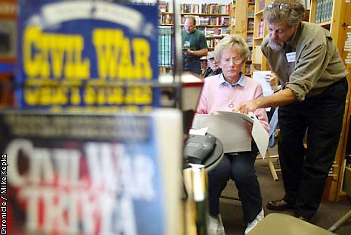 At Bay Book in San Ramon, Marylou Acorn of Danville and Ancestor Researcher Clay Feeter look some found information about Acorn's great grandfather who wagon mastinon during the Civil War. BY MIKE KEPKA/THE CHRONICLE