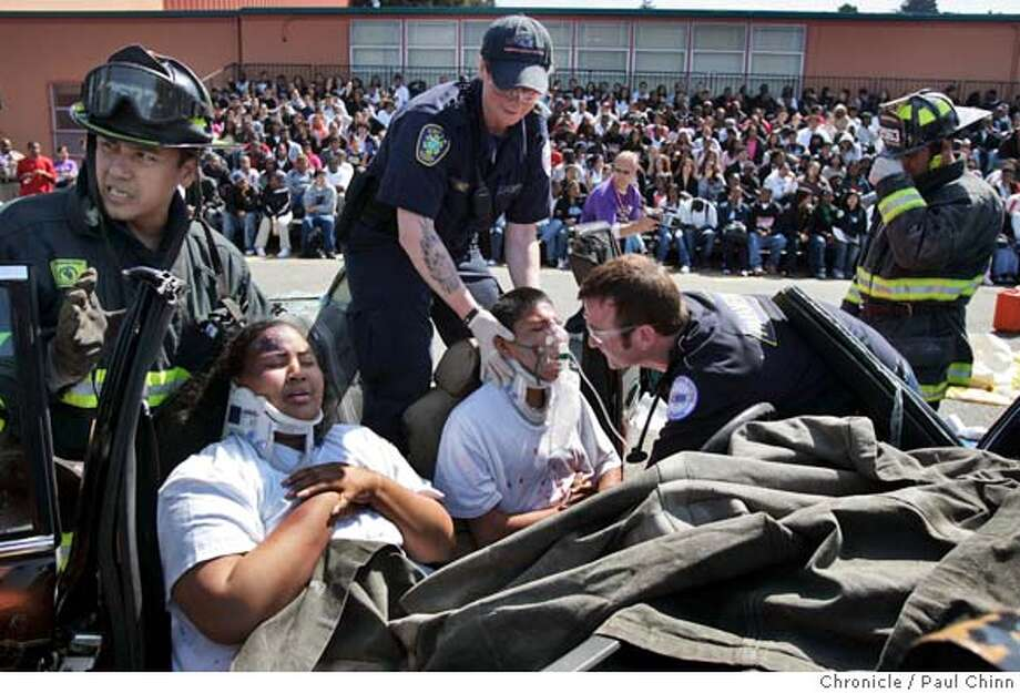 "mockcrash13_106_pc.jpg  Crash ""victims"" Brianna Travis (left) and Jovanny Montano are treated by firefighters and paramedics as classmates watch in the background. The California Highway Patrol stages a mock drunken driving accident at Castlemont High School on 5/12/05 in Oakland, Calif. The staged car crash - the result of illegal ""sideshow"" activity - demonstrated for students the dangers of DUI. PAUL CHINN/The Chronicle MANDATORY CREDIT FOR PHOTOG AND S.F. CHRONICLE/ - MAGS OUT Photo: PAUL CHINN"