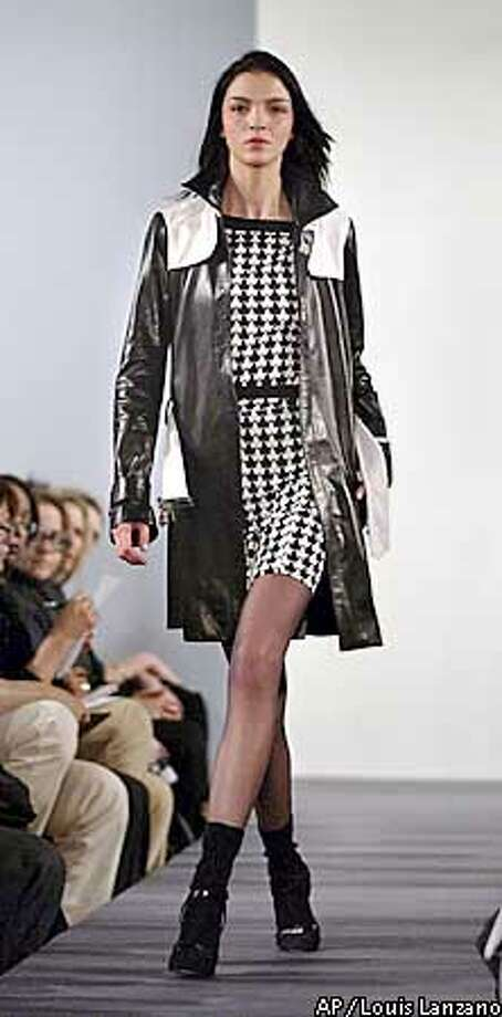 A model wears a houndstooth silk jersey dress under a black and white leather trench coat during the showing of the fall 2003 collection of Diane Von Furstenberg in New York, Sunday, Feb. 9, 2003. (AP Photo/Louis Lanzano) Photo: LOUIS LANZANO