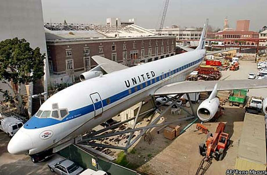 SPECIAL TO THE SAN FRANCISCO CHRONICLE- A United Airlines DC8 is surrounded by construction equipment on the grounds of the new Science Center School, Tuesday, Jan. 28, 2003, in Los Angeles. The school, under construction at the rear of the plane, will serve kindergarten through fifth grade and is a joint project between the Los Angeles Unified School District and the California Science Center. To the left of the plane is the the Science Center's old Armory Building, which is being renovated to house additional classroom space and the Amgen Center for Science Learning. The plane, which was donated by the airline to the California Museum of Science and Industry, will serve as a drop-off and pick-up hub for parents and their children at the entry to the campus. (AP Photo/Rene Macura) Photo: RENE MACURA