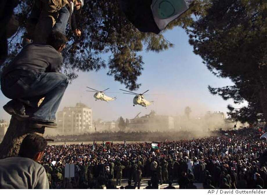 Two Egyptian helicopters carrying the remains of Palestinian leader Yasser Arafat and Palestinian leaders, come in to land over crowds of mourners, at Arafat's compound in the West Bank town of Ramallah, prior to a burial service Friday Nov 12, 2004. (AP Photo/David Guttenfelder) Photo: DAVID GUTTENFELDER