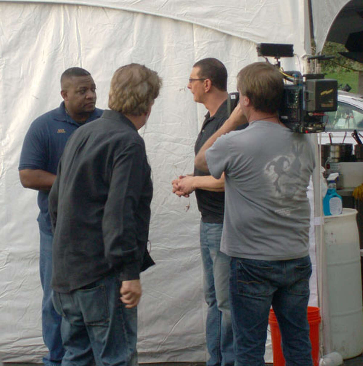 Mama Lee's Soul Food restaurant owner Ken Lee (far left) listens to advice from TV celebrity chef Robert Irvine (rear right) Monday as television crew members tape the exchange for broadcast on Irvine's