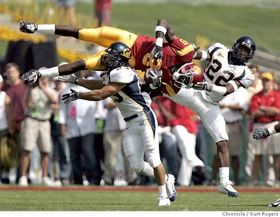 Dwayne Aarrett of usc caught this pass in the first quarter for a first down Cal's Ryan Gutierrez and Tim Mixon defending on the play.  The University of California Berkeley Golden Bears vs the University of Southern California Trojans at the Los Angeles Memorial Coliseum.  CAL_68_kr.JPG 10/9/04 in Los Angeles,CA.  KURT ROGERS/THE CHRONICLE MANDATORY CREDIT FOR PHOTOG AND SF CHRONICLE/ -MAGS OUT Sports#Sports#Chronicle#11/17/2004#ALL#5star##0422404169 Photo: KURT ROGERS