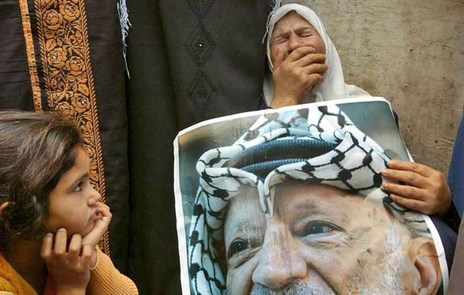 A young girl watches a Palestinian woman weep at Arafat's Ramallah compound after news of his death broke Thursday,