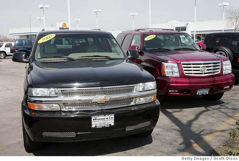 SCHAUMBURG, IL - APRIL 25: Chevrolet Suburban (L) and a Cadilac Escalade (R) sport utility vehicles sit on the lot of a suburban Chicago dealership April 25, 2005 in Schaumburg, Illinois. General Motors announced today that it would recall more than two million full-size pickup trucks and sport utility vehicles from the 2003 to 2005 model years, including the Suburban and Escalade, because of defective second-row seat belts. (Photo by Scott Olson/Getty Images) Ran on: 04-26-2005  A Chevrolet Suburban and a Cadillac Escalade, both sport utility vehicles, sit on the lot of a suburban Chicago dealership. Photo: Scott Olson