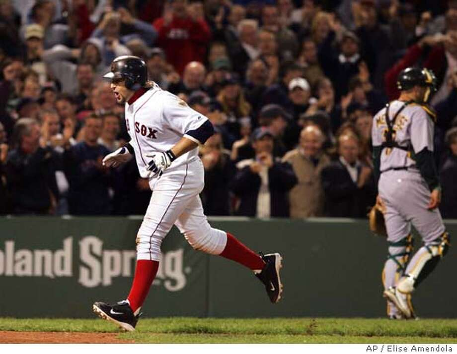 Boston Red Sox's Kevin Millar celebrates as he heads to the plate while Oakland Athletics catcher Adam Melhuse leaves the field after Millar's walk-off two-run homer to beat the Oakland Athletics 3-2 in the ninth inning at Fenway Park in Boston Tuesday, May 10, 2005. (AP Photo/Elise Amendola) Photo: ELISE AMENDOLA
