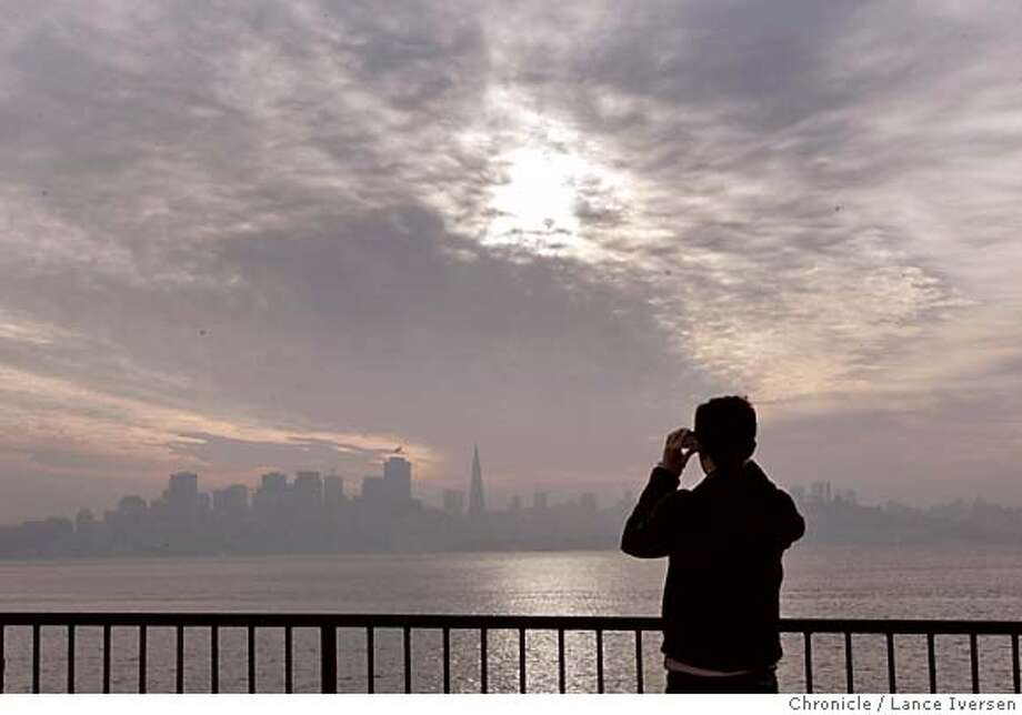 FEATURE_033.jpg_  Michael Nshanian (cq) from San Jose takes a pitcure of the San Francisco skyline from Treasure Island as a buttermilk sky covers the bay Area Tuesday. By Lance Iversen/San Francisco Chronicle MANDATORY CREDIT PHOTOG AND SAN FRANCISCO CHRONICLE. Metro#Metro#Chronicle#11/17/2004#ALL#5star##0422470645 Photo: Lance Iversen