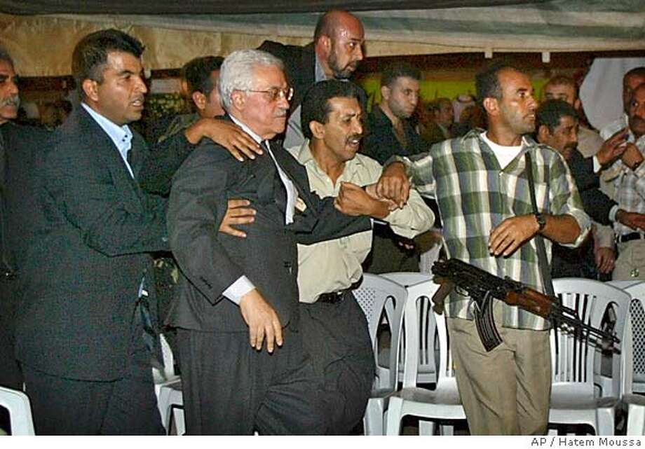 ** RETRANSMISSION TO CLARIFY CAPTION ** Bodyguards take away Mahmoud Abbas, former Palestinian Prime Minister and the succesor of Yasser Arafat as PLO chief, after gunfire erupted at the tent set up for mourners to gather in memory of Arafat in Gaza city Sunday Nov. 14, 2004. One security guard was killed and five people were wounded, hospital officials said. (AP Photo/Hatem Moussa) Photo: HATEM MOUSSA