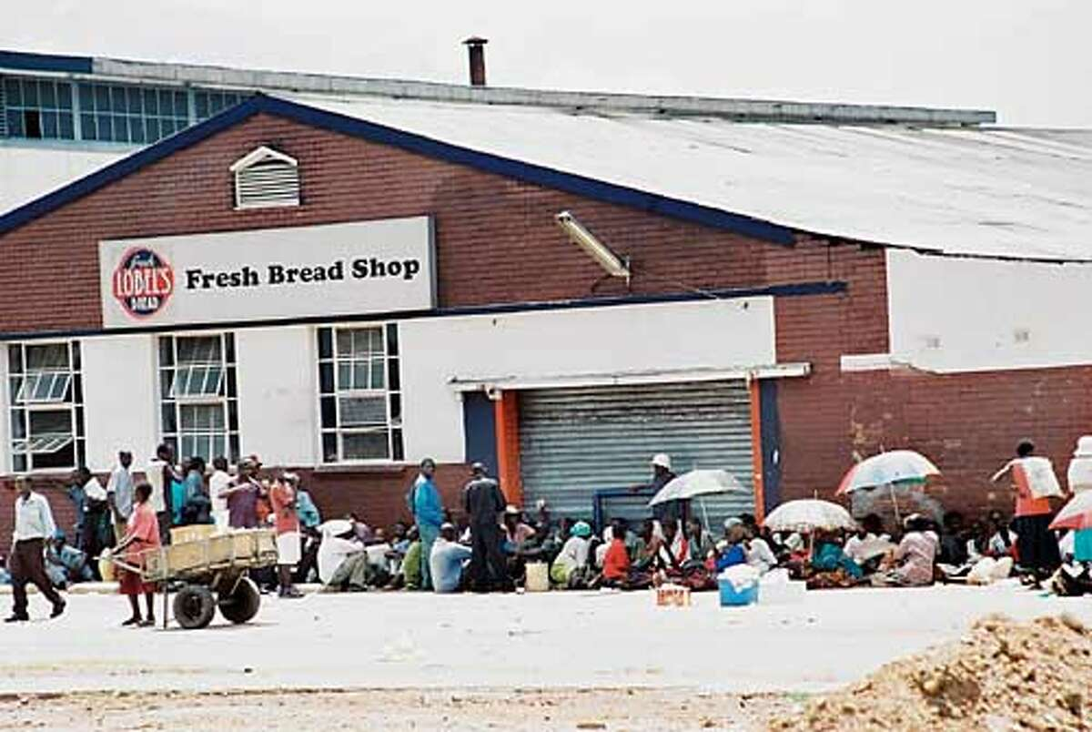 People wait hours for loaves of price-controlled bread to go on sale in downtown Harare, Zimbabwe. Photo by Gavin du Venage, special to the Chronicle