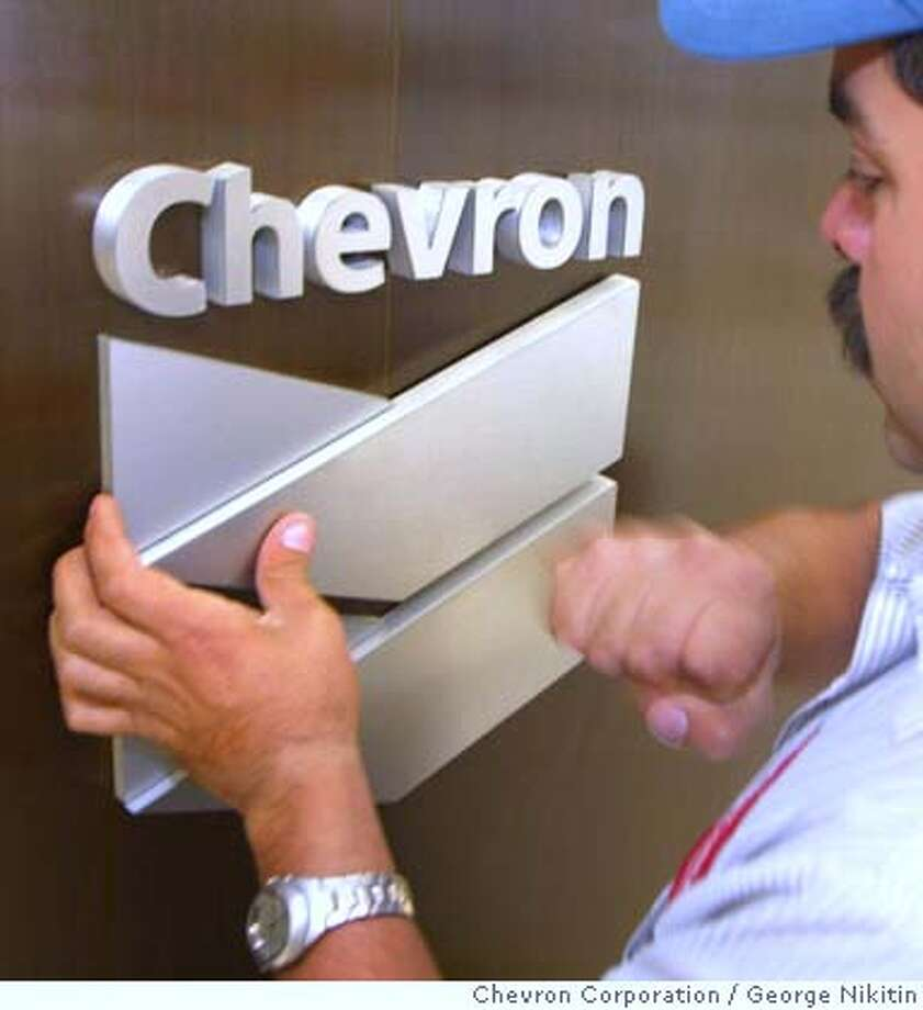 EMBARGO UNTIL MAY 9, 2005, 8 AM PACIFIC TIME--Sign installer David Valdivia installs Chevron Corporation's new company logo at corporate headquarters, Monday May 9, 2005 in San Ramon, California. ChevronTexaco announced today that it is changing its name to Chevron Corporation in a move to present a clear, strong and unified presence in the global marketplace. (Photo/ho, George Nikitin, Chevron Corporation) Photo: GEORGE NIKITIN