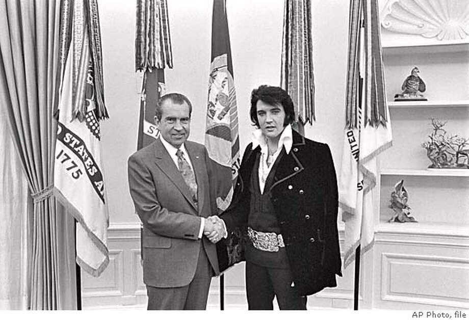 Undated black-and-white photo released by the National Archives showing President Nixon shaking hands with entertainer Elvis Presley in the Oval Office, part of an exhibit at the National Archives in Washington entitled: The Publics Vaults. The National Archives, best known as the repository for the original copies of the Declaration of Independence and Constitution, has dusted off more than 1,000 relics and put them on public display. (AP Photo/National Archives) NATIONAL ARCHIVES PHOTO Datebook#Datebook#Chronicle#11/15/2004#ALL#5star##0422464108 Photo: OLIVER F. ATKINS
