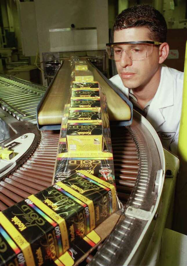 A Kodak technician Dan Merola inspects boxes of Kodak Royal Gold film coming off a packaging line in Rochester, N.Y. in an undated  photo released by Kodak.   Eastman Kodak Co., struggling to find its footing in new digital photography markets as its signature film business fades, said Thursday it will cut 12,000 to 15,000 jobs, or up to 23 percent of its global work force, over the next three years. Photo: AP / EASTMAN KODAK CO.