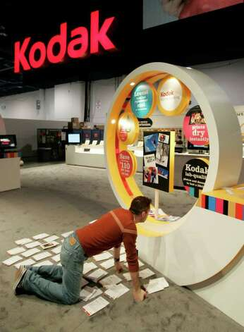 In this Jan. 9, 2009 file photo, Kodak's Jim Nunes helps set up Kodak booth at the International Consumer Electronics Show (CES) in Las Vegas. Eastman Kodak Co. said Thursday, Jan. 29, 2009, it is cutting 3,500 to 4,500 jobs, or 14 percent to 18 percent of its work force, as it posted a fourth-quarter loss of $137 million on plunging sales of both digital and film-based photography products. Its stock tumbled more than 23 percent. Photo: Paul Sakuma, AP / AP