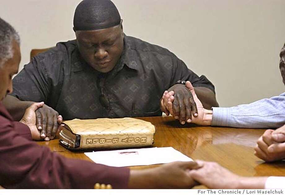 Baton Rouge, Louisiana May 4, 2005  Michael Williams, left, prays with employeers of the Baker Printing, a small business in Baker, Louisiana. Williams was invited to speak at the print shop's weekly staff prayer meeting.  Photo by Lori Waselchuk/For The Chronicle Photo: Lori Waselchuk/For The Chronicle