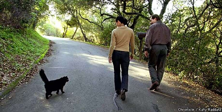 "PHOTO BY KATY RADDATZ--THE CHRONICLE  Feature on the Wildlife Conservation Network, cofounded by Charlie Knowles and Akiko Yamazaki. SHOWN: Charlie (R) and Akiko (R) walk in the hills near their office accompanied by ""Wolfgang"", Charlie's cat. Photo: KATY RADDATZ"