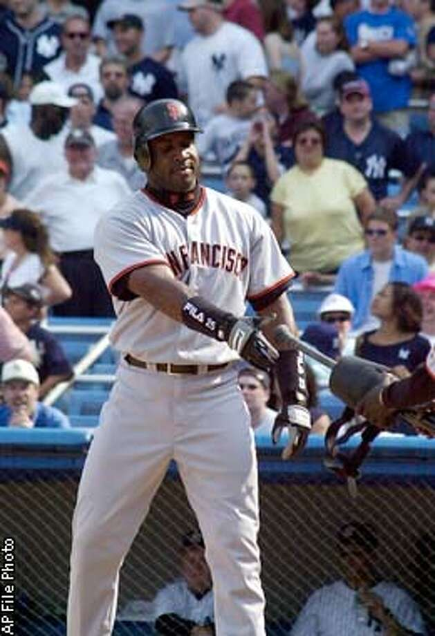 San Francisco Giants' Barry Bond hands a bat and gear to a ball boy after being walked intetionally in the ninth inning against the New York Yankees Sunday, June 9, 2002 at Yankee Stadium in New York. Bonds was walked intentionally three times, tying a career high. (AP Photo/Osamu Honda) Photo: OSAMU HONDA