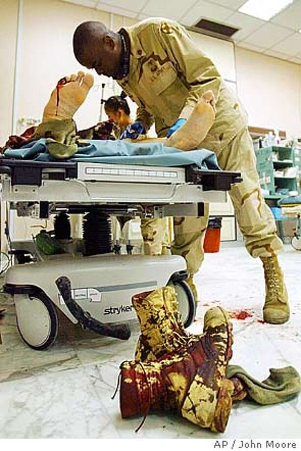 Sgt. 1st Class Rodney Chiles checks the wounds of a U.S. Marine suffering from injuries from a roadside bomb, after being evacuated to a military hospital in Baghdad, Iraq Tuesday, Nov. 9, 2004. Chiles is from Langston, OK.(AP Photo/John Moore) Insight#Insight#Chronicle#11/14/2004##2star##0422458685 Photo: JOHN MOORE