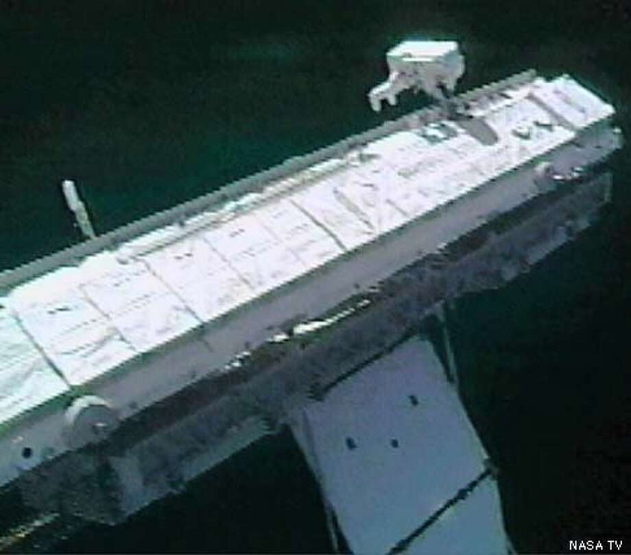 science officer Don Pettit is seen at the end of the 45 foot long P1 truss as he works to prepare the truss' center radiator for deployment January 15, 2003. Pettit and Commander Ken Bowersox experienced a delay in their EVA caused by a balky outer hatch handle on the Qwest airlock. NASA TV Photo Photo: NASA TV