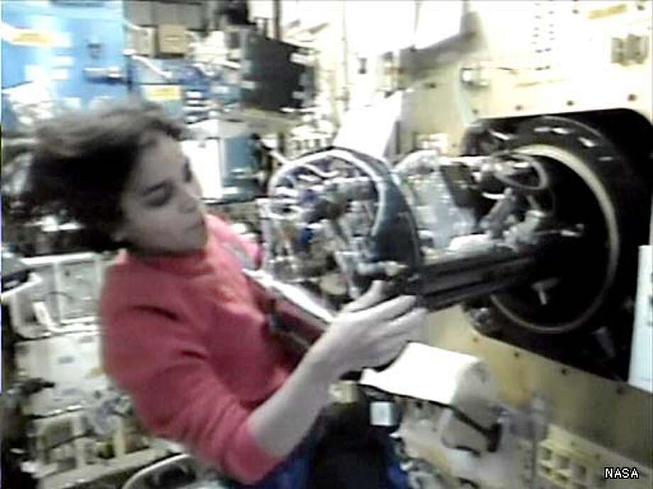 ** FILE ** In this image from television on Tuesday Jan. 28, 2003, shuttle mission specialists Kalpana Chawla pulls the combustion module from it's mounting in the SPACEHAB research Module abord the shuttle Columbia. Columbia's astronauts joined Mission Control in a moment of silence Tuesday at the exact time 17 years ago that Challenger exploded in the sky. NASA lost communication with Columbia as the ship soared over Texas several minutes before landing Saturday morning Feb. 1, 2003. It wasn't immediately clear if there was a problem with the shuttle. (AP Photo/NASA TV, File)