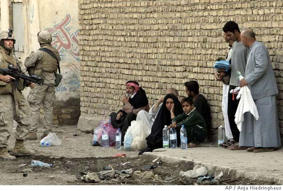 An Iraqi family who tried to flee fighting in the center of Fallujah, Iraq, shelter next to a wall, as U.S. Marines look on Friday, Nov. 12, 2004. Hundreds of men trying to flee the assault on Fallujah have been turned back by U.S. troops following orders to allow only women, children and the elderly to leave. (AP Photo/Anja Niedringhaus) Photo: ANJA NIEDRINGHAUS