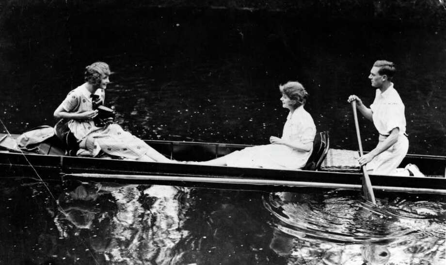 A girl takes a photograph of her friends with a large Kodak camera, while sailing in a punt. Photo: Hulton Archive, Getty Images / Hulton Archive