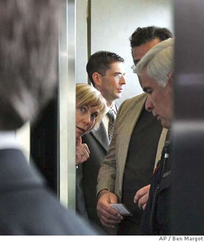 Prosecutor Birgit Fladager, peaks out from the elevator as fellow prosecutor Rick Distaso is seen behind her, as they leave the courthouse after the verdict was read in the Scott Peterson case, in Redwood City, Calif., Friday, Nov. 12, 2004. Peterson was found guilty of two counts of murder. (AP Photo/Ben Margot) Photo: JEFF CHIU