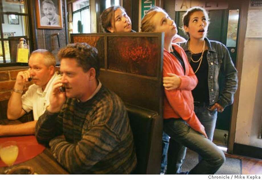 Gervasonis Restaurant patrons, Todd Vincent and Steve Faughn recite the Peterson verdict to friends over the phone while Kylie Holl, 15, Melissa Malone, 15 and Elizabeth Derieux, 15 look up at the TV as details about the verdict are told.  The people of Modesto react to the Scott Peterson guilty verdict. 11/12/04  Mike Kepka/The Chronicle Photo: Mike Kepka