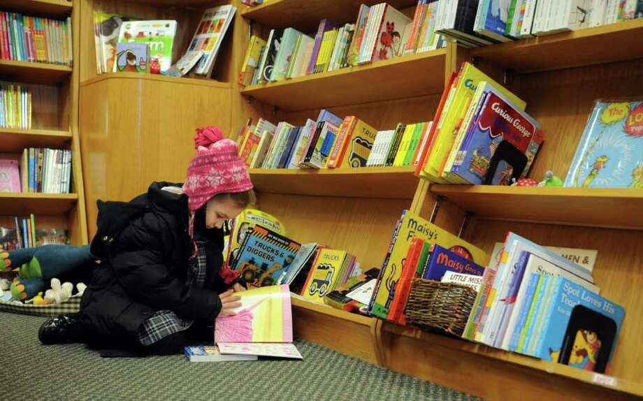 Chloe Gerace, 5, flips through a book at Barrett Bookstore in Darien on Friday, January 13, 2012. Photo: Lindsay Niegelberg / Stamford Advocate