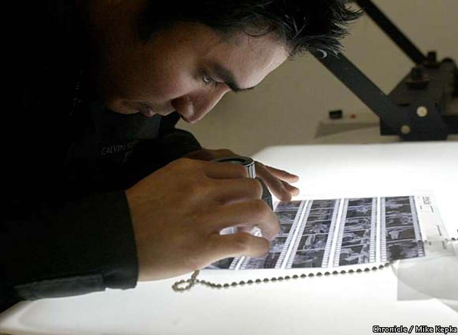 John Laxa, 29, of Walnut Creek studies his negatives on the light table at the Darkroom in Martinez. Chronicle photo by Mike Kepka