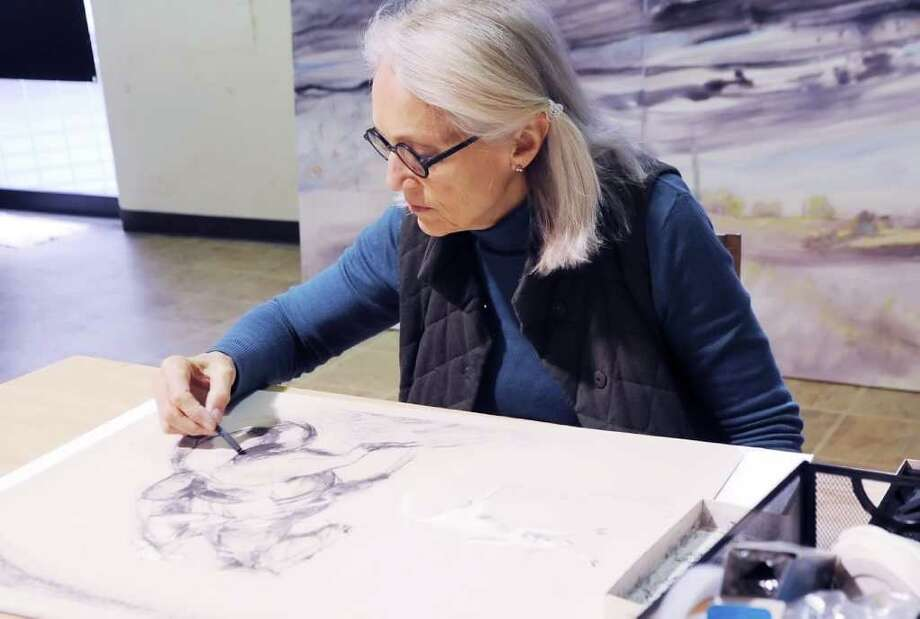"Greenwich artist Marian ""Bing"" Bingham paints in her studio Thursday, Jan. 19, 2012. She is awaiting the return of several of her paintings, which were seized a few months ago along the Serbian border en route to a European exhibition. Photo: Helen Neafsey / Greenwich Time"