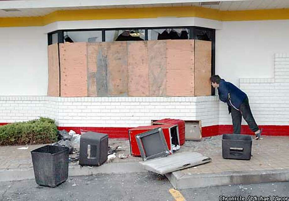 Sonia Gavara, an employee at McDonald's at 63rd and International in Oakland, tries to see through the boarded-up windows. The restaurant was trashed by rioters after the Raiders' Super Bowl loss. Chronicle photo by Michael Macor