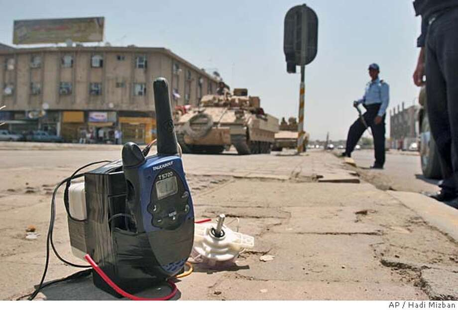 US Army and Iraqi police secure the area after they found a suicide car and this remote control device in the centre of Baghdad, Iraq, Friday, May 6, 2005. Iraqi police discovered the car before it exploded, finding home made TNT bombs in the trunk of the vehicle. (AP Photo/Hadi Mizban) Photo: HADI MIZBAN