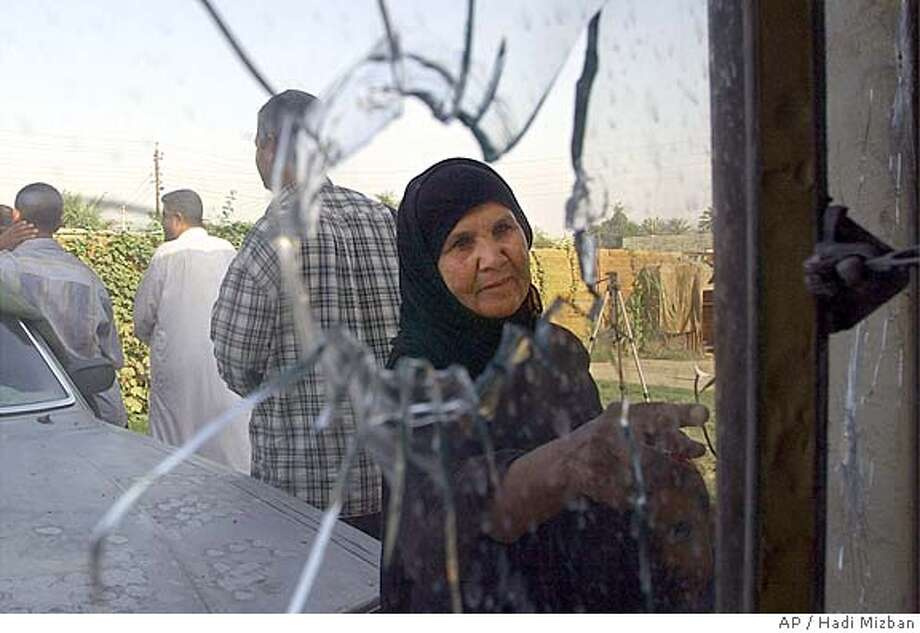 A neighbor looks at bullet holes in the window of her home across the street from the Allawi family kidnapping scene in Baghdad, Iraq Wednesday Nov. 10, 2004. Two members of Iraqi Prime Minister Ayad Allawi's family were abducted from their Baghdad home Tuesday evening, including his cousin, Ghazi Allawi, and his cousin's daughter-in law. A posting on an Islamic Website by a group calling itself Ansar al-Jihad group claimed responsibility for kidnapping three of Allawi's relatives, and threatened to behead them in 48 hours if their demands aren't met. (AP Photo/Hadi Mizban) Ran on: 11-11-2004  A neighbor looks at bullet holes in the window of her home across the street from the Allawi family kidnapping scene in Baghdad. Photo: HADI MIZBAN